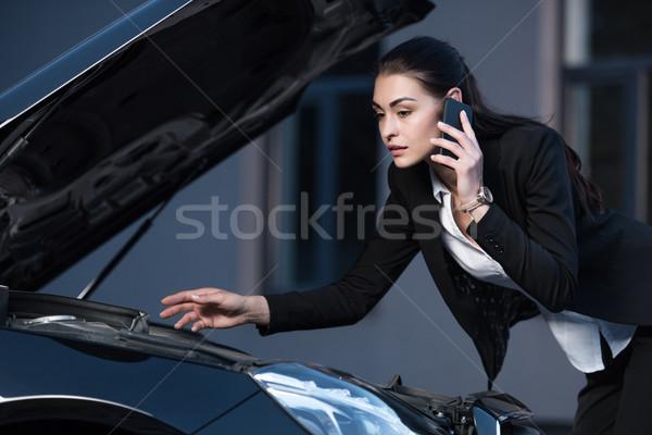 woman looking under hood of car Stock photo © LightFieldStudios