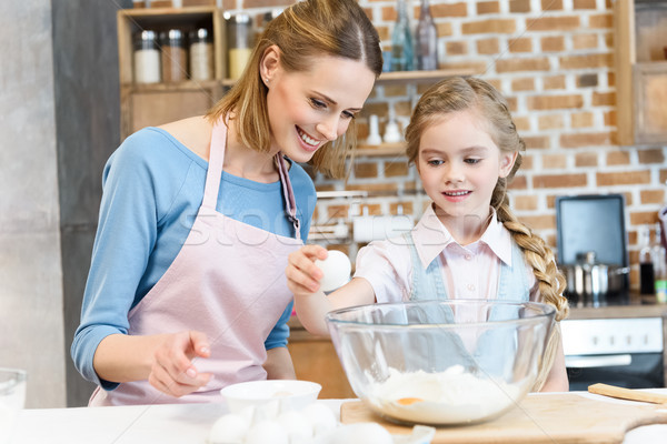 Happy mother looking at daughter beating egg in glass bowl with flour  Stock photo © LightFieldStudios