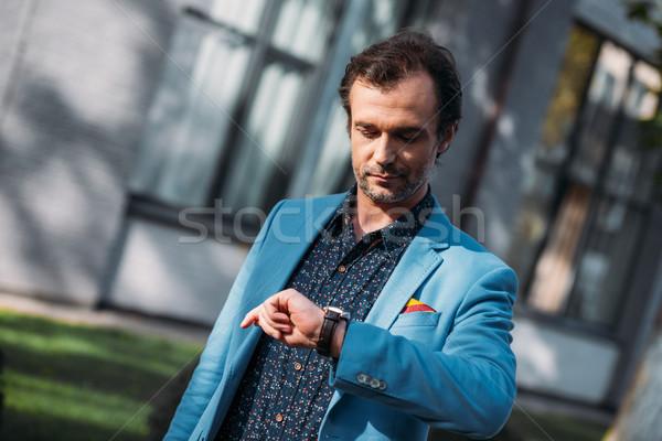 man checking wristwatch Stock photo © LightFieldStudios