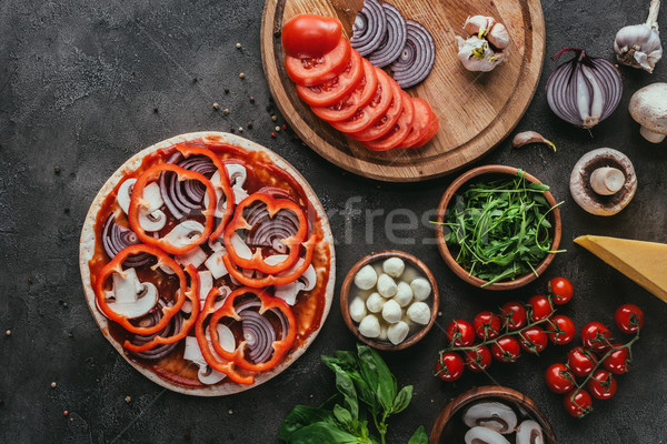 top view of uncooked pizza with ingredients on concrete table Stock photo © LightFieldStudios