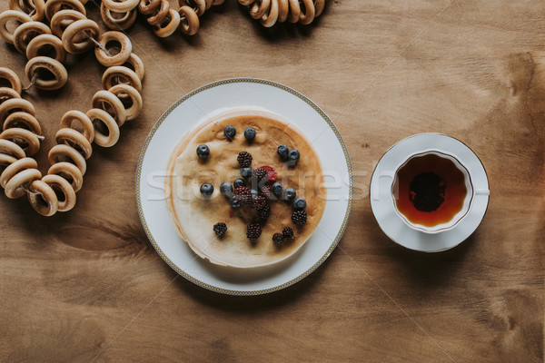 top view of tasty pancakes with berries, cup of tea and bagels on wooden table  Stock photo © LightFieldStudios