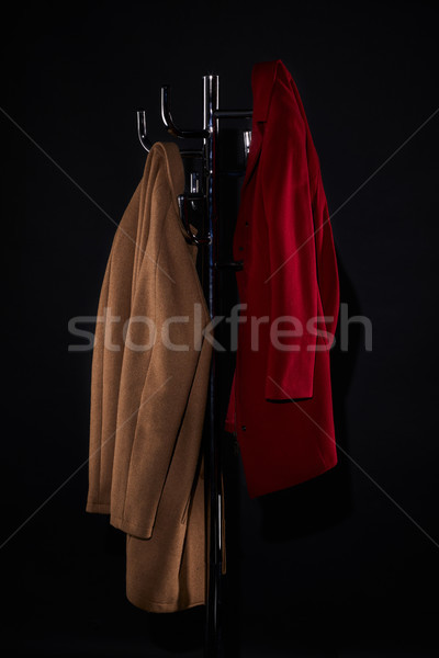 classic coats on coat rack isolated on black Stock photo © LightFieldStudios