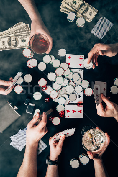 Smoke over people with alcohol in glasses playing poker by casino table with money and chips Stock photo © LightFieldStudios