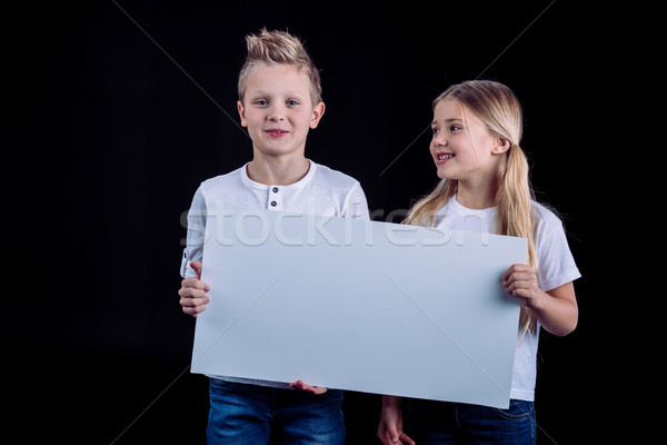 Smiling siblings with blank card Stock photo © LightFieldStudios