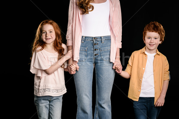Mother with adorable redhead children standing together and holding hands isolated on black Stock photo © LightFieldStudios