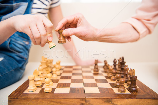 Close-up partial view of girl and senior woman playing chess Stock photo © LightFieldStudios
