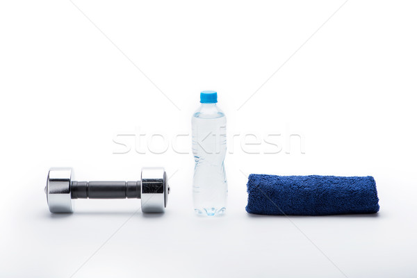 metallic dumbbell, towel and bottle with water isolated on white. equipment sport and healthy living Stock photo © LightFieldStudios