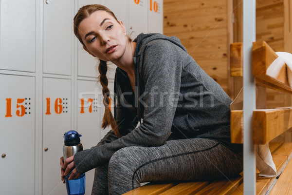 Woman sitting on bench in locker room Stock photo © LightFieldStudios