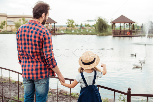 Família olhando lagoa parque ver de volta pai Foto stock © LightFieldStudios