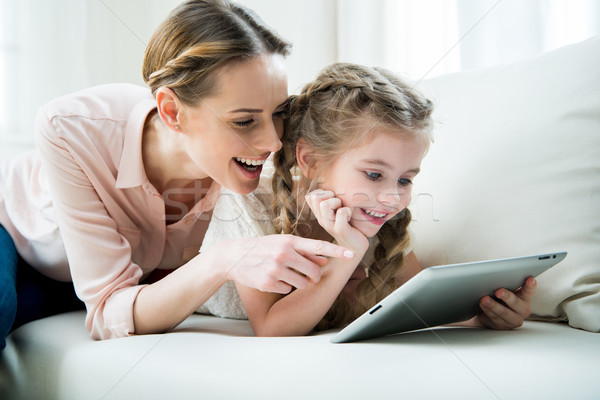 portrait of cheerful mother and daughter using tablet at home Stock photo © LightFieldStudios