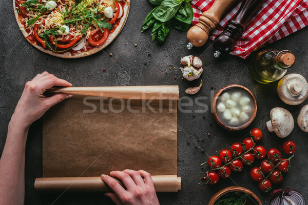 cropped shot of woman with parchent paper preparing pizza on concrete table Stock photo © LightFieldStudios