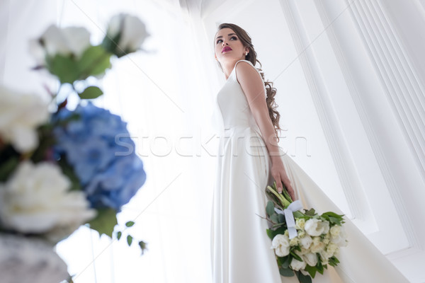 bottom view of bride posing in white dress with wedding bouquet Stock photo © LightFieldStudios