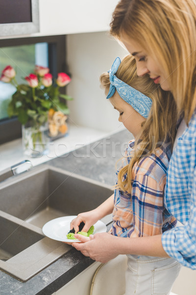side view of little daughter helping mother to wash dishes after dinner at home Stock photo © LightFieldStudios