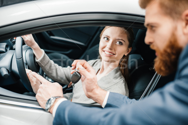 Bearded salesman giving car key to smiling young woman sitting in new car  Stock photo © LightFieldStudios