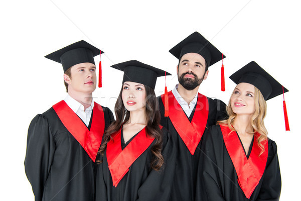 Group of young men and women in graduation caps looking up on white Stock photo © LightFieldStudios