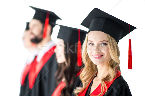attractive student in graduation cap with diploma, with friends behind isolated on white Stock photo © LightFieldStudios