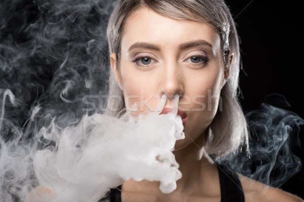 Young woman vaping and blowing smoke of electronic cigarette from nose Stock photo © LightFieldStudios
