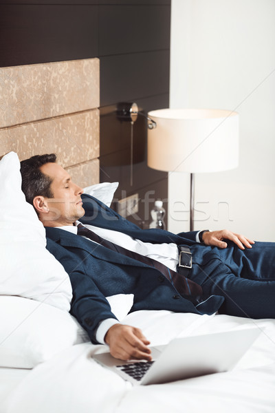 Businessman napping in hotel room Stock photo © LightFieldStudios