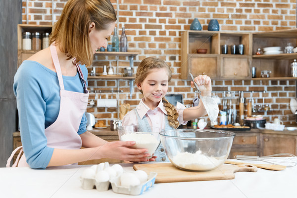 Stock photo: Happy mother and daughter preparing dough and cooking together in kitchen