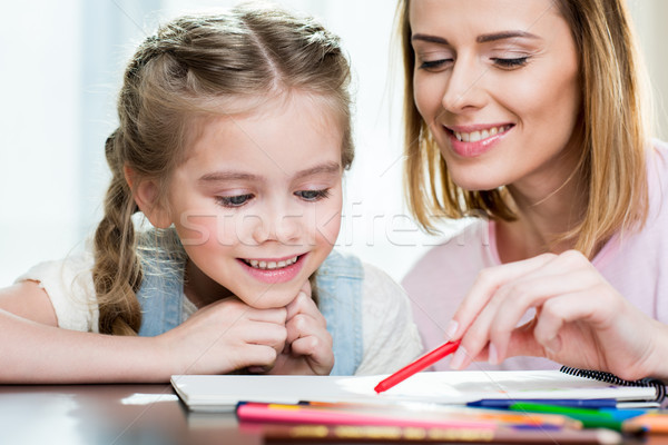 Stock photo: Happy mother and daughter drawing at home