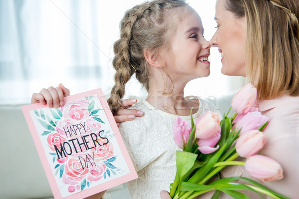 side view of smiling daughter greeting mother with tulips and postcard on mother's day Stock photo © LightFieldStudios