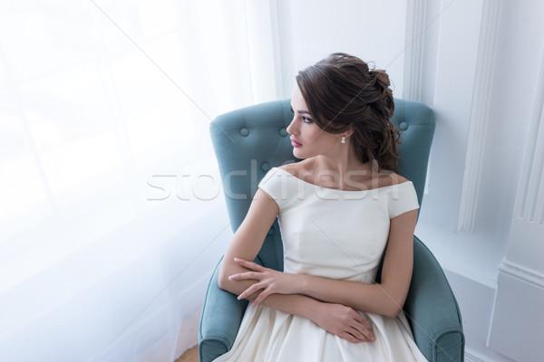 brunette woman in wedding dress sitting in armchair and looking at window Stock photo © LightFieldStudios