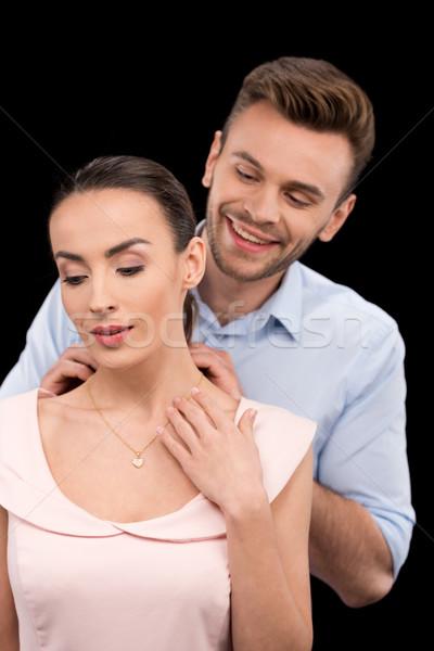 portrait of smiling man putting jewelry on woman's neck on black, International womens day concept Stock photo © LightFieldStudios