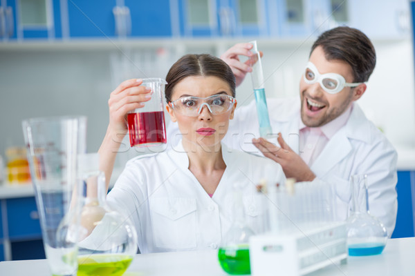 Excited man and woman scientists in protective glasses working with reagents in lab Stock photo © LightFieldStudios