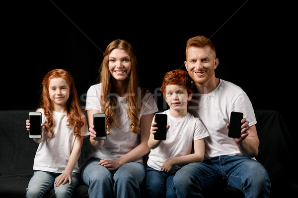 smiling family showing smartphones isolated on black Stock photo © LightFieldStudios