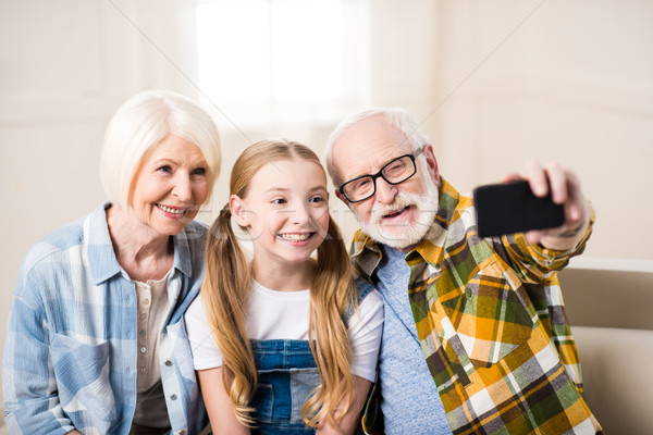 Happy girl with grandmother and grandfather sitting on sofa and taking selfie Stock photo © LightFieldStudios