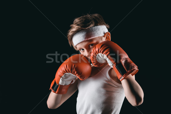 boy obscuring face with boxing gloves isolated on black, active kids concept Stock photo © LightFieldStudios