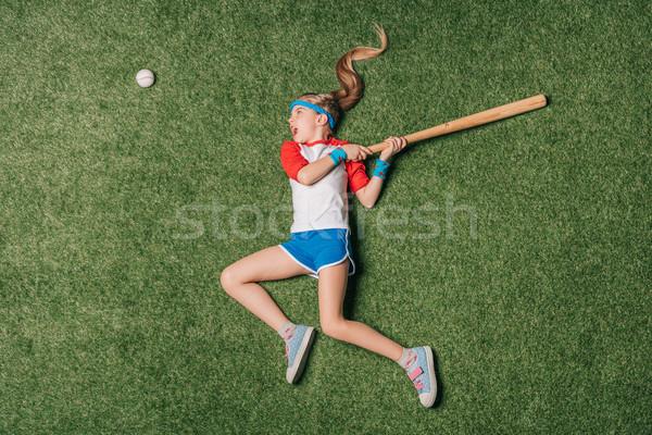 top view of little girl pretending playing baseball on grass, athletics children concept Stock photo © LightFieldStudios