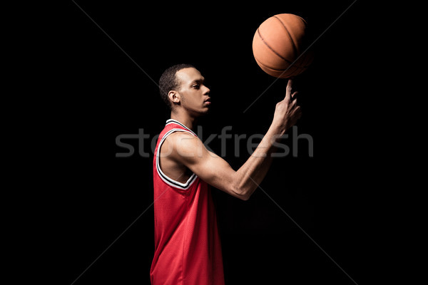 Side view of athletic basketball ball holding ball on finger Stock photo © LightFieldStudios