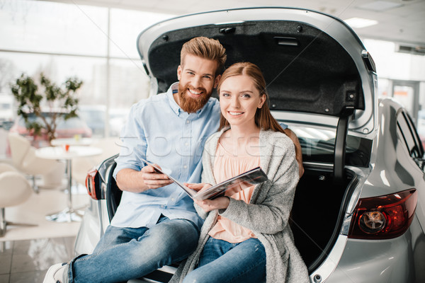 Happy couple with catalog sitting on car trunk in dealership salon   Stock photo © LightFieldStudios