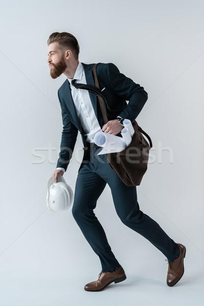 Fiatal üzletember védősisak tervrajzok váll táska Stock fotó © LightFieldStudios