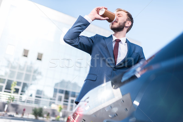 Stock photo: businessman drinking coffee at car