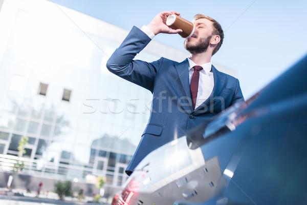 businessman drinking coffee at car Stock photo © LightFieldStudios