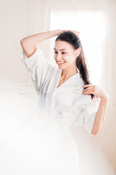Smiling woman in bathrobe with cream on face Stock photo © LightFieldStudios