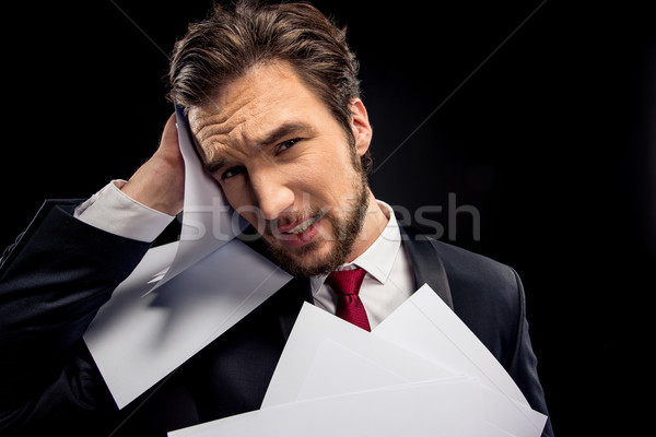 Upset businessman holding papers  Stock photo © LightFieldStudios