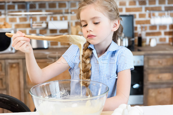 Pensive little girl holding wooden spoon and looking at dough in glass bowl Stock photo © LightFieldStudios