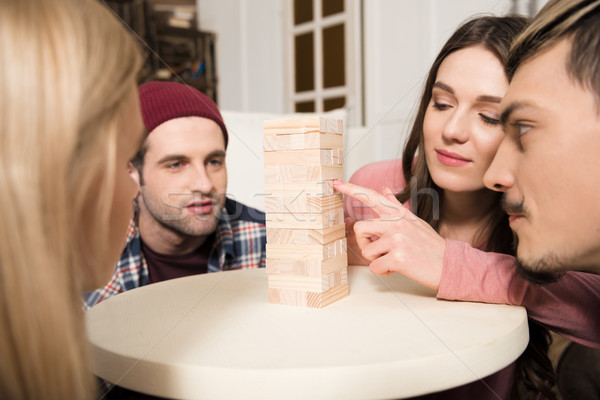 side view of focused friends playing jenga game together at home Stock photo © LightFieldStudios
