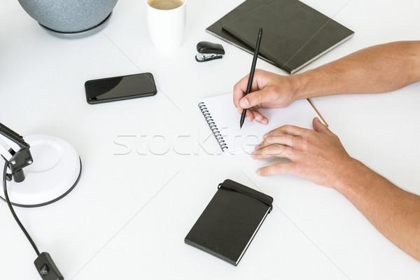 Człowiek piśmie notatnika shot biały tabeli Zdjęcia stock © LightFieldStudios