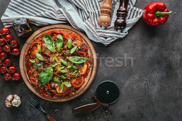 top view of freshly baked pizza with cutter and ingredients on concrete table Stock photo © LightFieldStudios