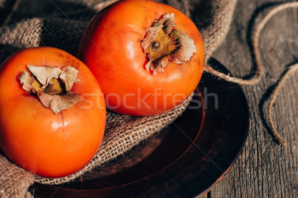 two ripe persimmons on sackcloth on wooden table Stock photo © LightFieldStudios