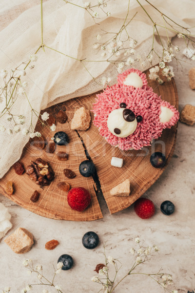 Stock photo: top view of delicious muffin in shape of bear with berries on wooden board