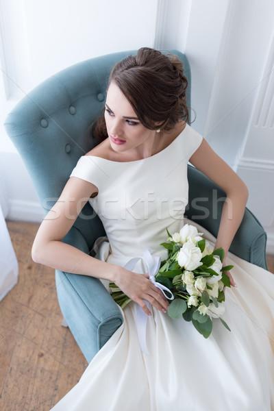 Atrakcyjny oblubienicy bukiet ślubny posiedzenia fotel kwiaty Zdjęcia stock © LightFieldStudios