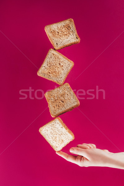 partial view of woman holding levitating toasts on finger isolated on pink Stock photo © LightFieldStudios