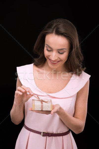 Young smiling woman in pink dress holding gift box on black, international womens day concept Stock photo © LightFieldStudios