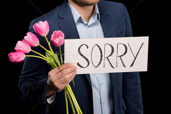 partial view of stylish man holding tulips bouquet and sorry sign on black Stock photo © LightFieldStudios