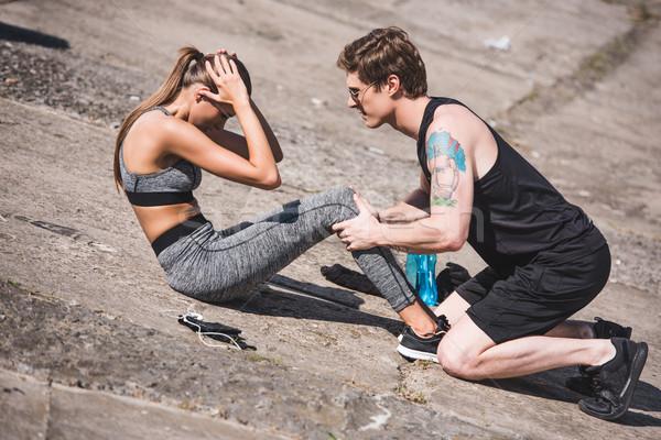 man helping sportive woman with training Stock photo © LightFieldStudios